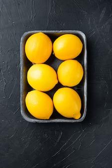 Rijpe citroenen set, in plastic bakje, op zwart
