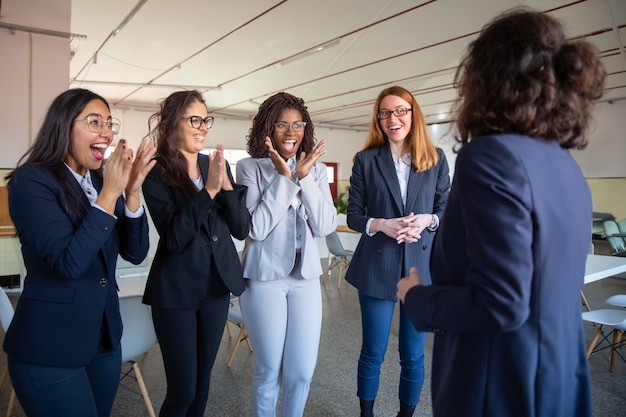 Rijpe collega die aan gelukkige jongere collega's spreekt