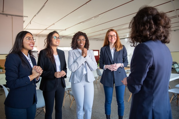 Rijpe collega die aan glimlachende jongere collega's spreekt