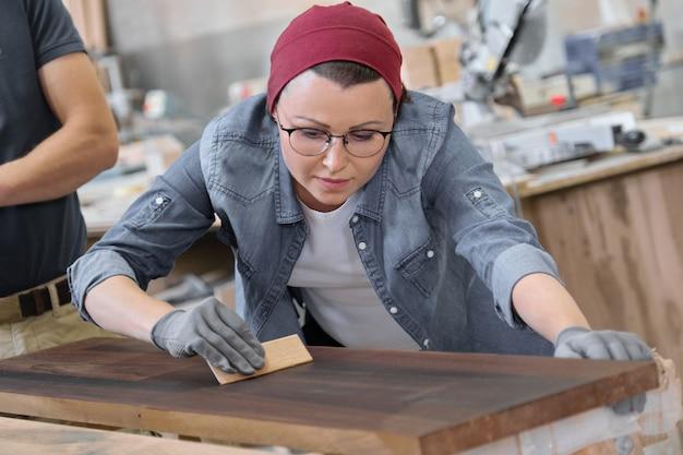 Rijpe craftswoman die in woodshop werkt.