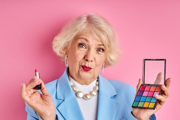 Rijpe dame die nieuwe productcosmetica toepast die op roze ruimte, schoonheidsconcept wordt geïsoleerd