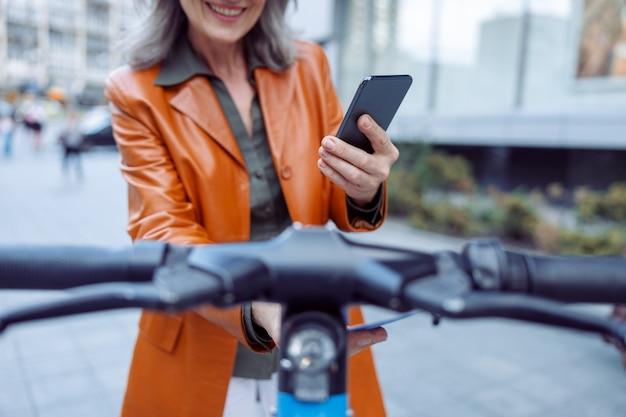 Rijpe dame met mobiele telefoon controleert prijs van elektrische scooter op stadsstraat