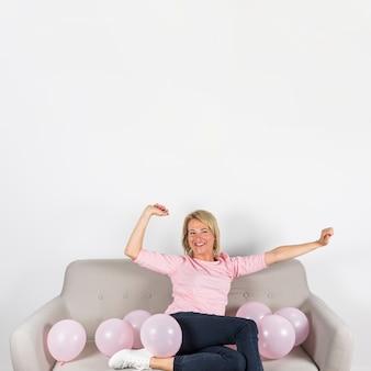 Rijpe de vrouwenzitting van de blonde op bank met ballons tegen witte achtergrond