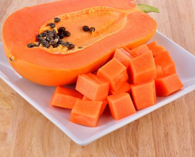 Rijpe die papaja op witte plaat wordt gesneden