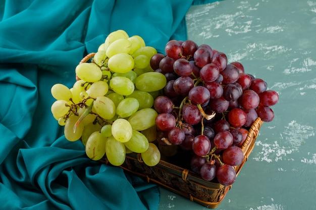 Rijpe druiven in een mand op gips en textiel. hoge kijkhoek.