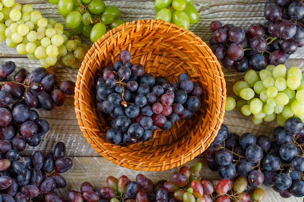 Rijpe druiven in een rieten mand op een houten achtergrond. plat leggen.