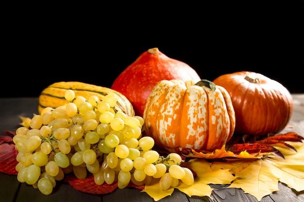 Rijpe druiven, merg en pompoenen op donkere houten en kleurrijke de herfstesdoornbladeren.