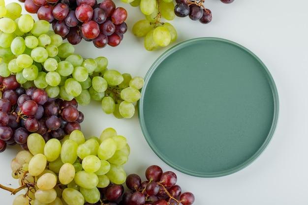 Rijpe druiven met een leeg dienblad plat leggen op een wit