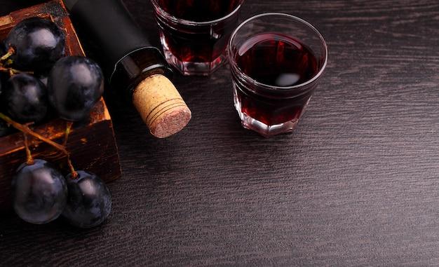 Rijpe druiven, rode wijn en een glas op een zwarte achtergrond