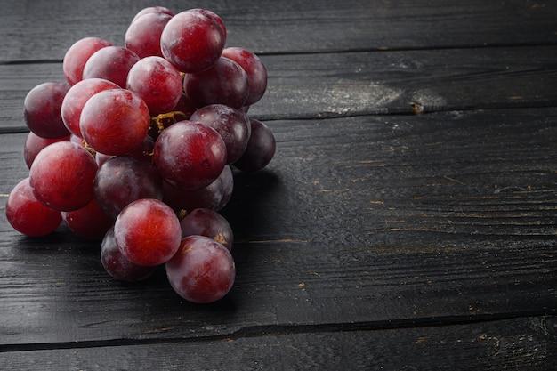 Rijpe druivenset, donkerrood fruit, op zwarte houten tafel