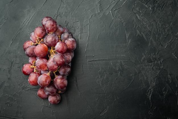 Rijpe druivenset, donkerrood fruit, op zwarte stenen tafel, bovenaanzicht plat