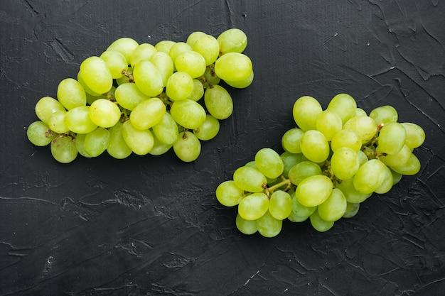 Rijpe druivenset, groen fruit, op zwarte stenen tafel, bovenaanzicht plat lag