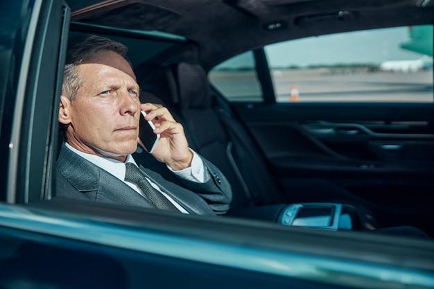 Rijpe elegante man belt in de auto terwijl hij wordt gedragen door de chauffeur na de landing op het vliegveld