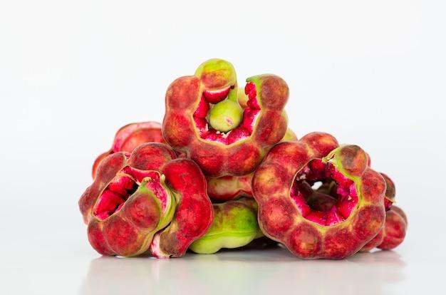 Rijpe en kleurrijke manilla tamarinde vruchten in peulvorm op wit