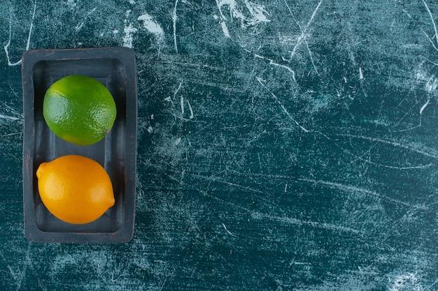 Rijpe en onrijpe citroen op een houten bord, op de marmeren tafel.