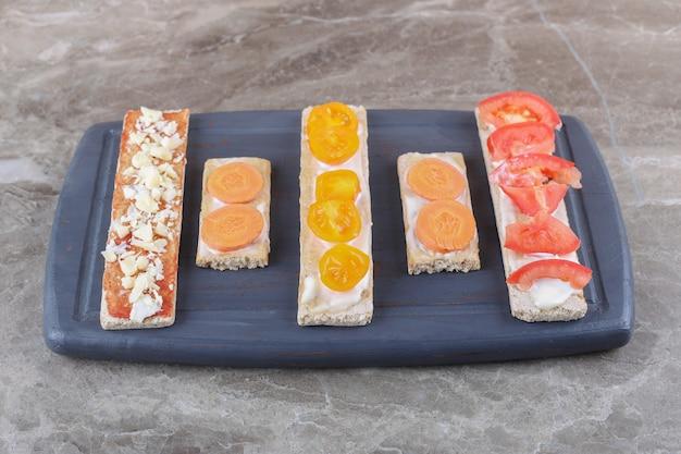 Rijpe en onrijpe tomaten gesneden op knapperige broden op de snijplank, op het marmeren oppervlak