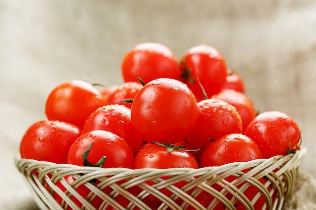 Rijpe en sappige cherrytomaten met druppels vocht in een rieten mand. oude houten tafel, rond het canvas van jute