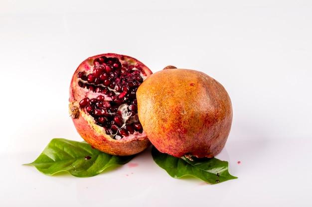 Rijpe en sappige granaatappel wordt in twee delen gesneden met bladeren op een witte achtergrond.