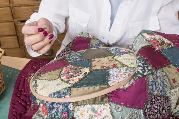 Rijpe en vrouw die naait quilt