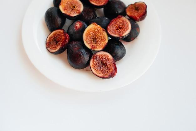 Rijpe en zoete vijgen gesneden en gerangschikt in een plaat op een witte achtergrond met vrije ruimte. fruit en vegetarisme.