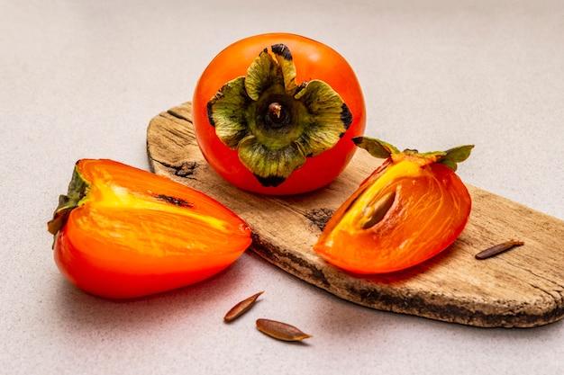 Rijpe enkele persimmon. vers geheel fruit, half gesneden, zaden. houten snijplank,