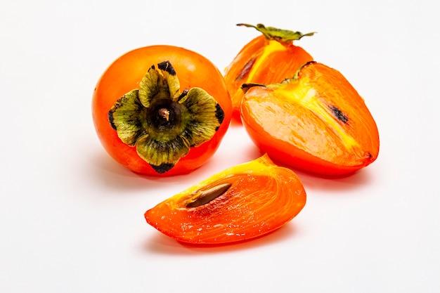 Rijpe enkele persimmon. vers geheel fruit, half gesneden, zaden.