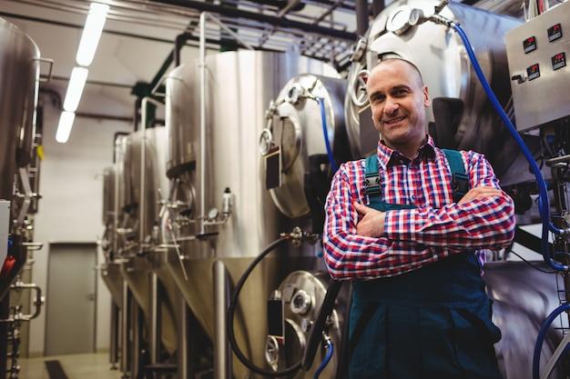 Rijpe fabrikant die zich door opslagtank bevindt in brouwerij