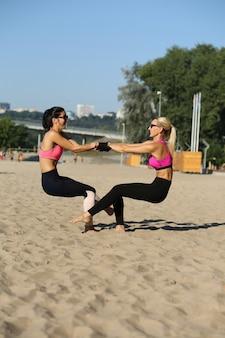 Rijpe fitnessvrouwen die sportkleding dragen, samen gehurkt op het strand