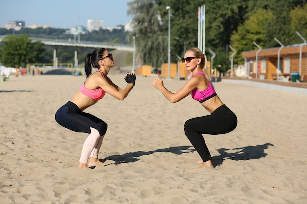 Rijpe fitnessvrouwen die sportkleding en zonnebril dragen die samen op het strand gehurkt zitten