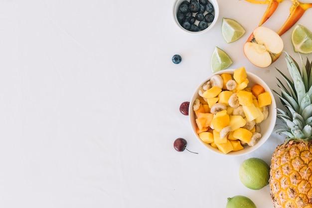 Rijpe fruitsalade die over witte achtergrond wordt geïsoleerd