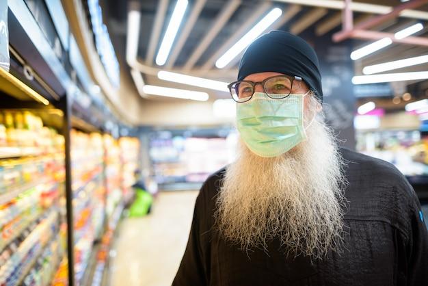 Rijpe gebaarde hipstermens met masker het kopen boodschappen terwijl het handhaven van afstand bij de supermarkt