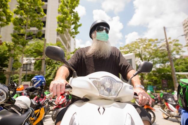Rijpe gebaarde hipstermens met zonnebril en masker berijdende motorfiets tijdens covid-19