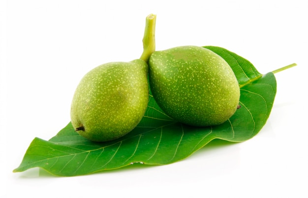 Rijpe gebroken walnoten met groene bladeren geïsoleerd op wit