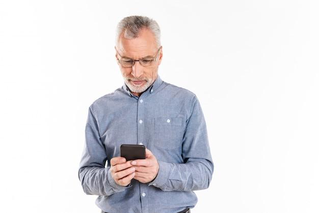 Rijpe geconcentreerde mens die geïsoleerde smartphone gebruiken