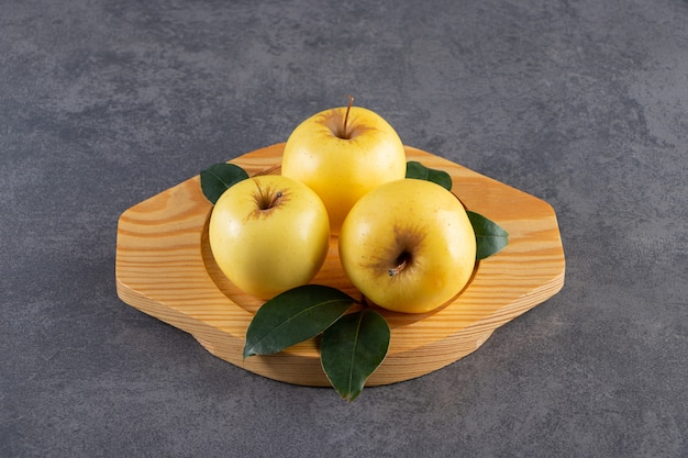 Rijpe gele appels met groene bladeren op houten plaat.