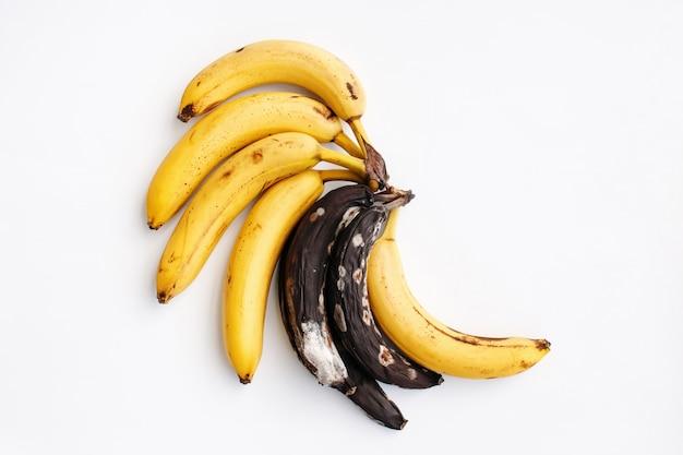 Rijpe gele bananen bedorven dichtbij gevormde bananen op wit