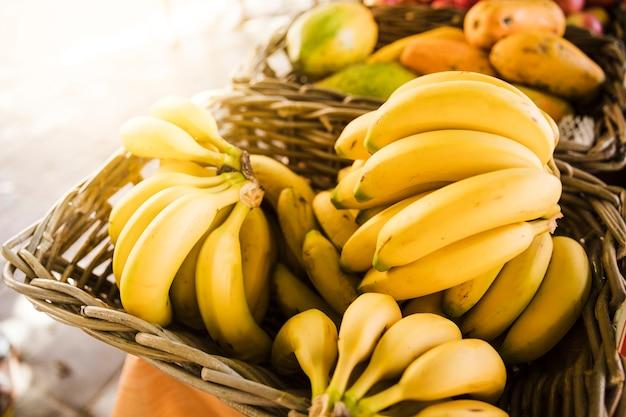 Rijpe gele bananen in rieten mand bij fruitmarktopslag