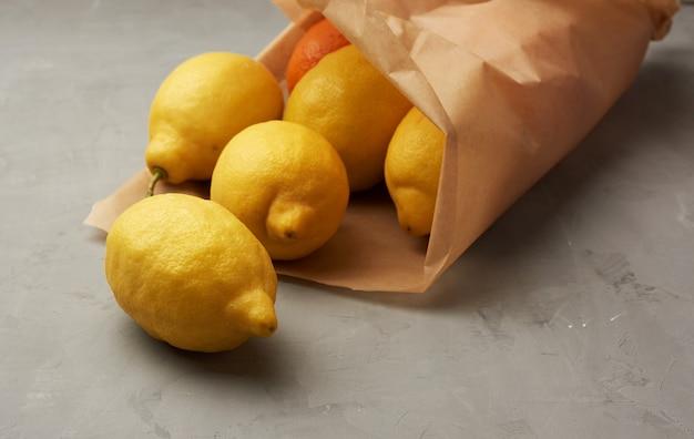 Rijpe gele citroenen in een bruine papieren zak op een grijze achtergrond