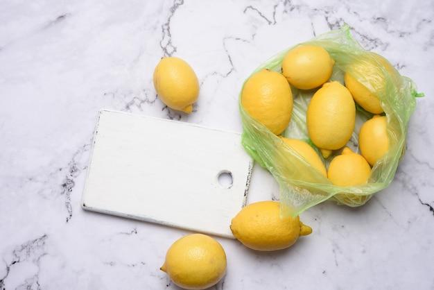 Rijpe gele citroenen op een witte houten plank, ingrediënt voor limonade, bovenaanzicht