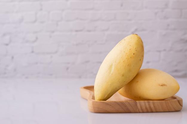 Rijpe gele mango's op wit bord.
