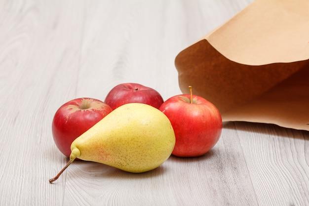 Rijpe gele peer en rode appels met een papieren zak op het houten bureau. gezonde biologische voeding.