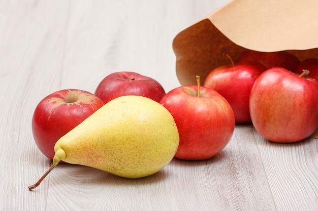 Rijpe gele peer en rode appels met papieren zak op houten bureau. gezonde biologische voeding.