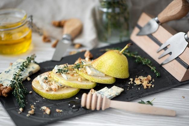 Rijpe gele peer met dor blauwe kaas, honing en walnoten op een kaasplankje