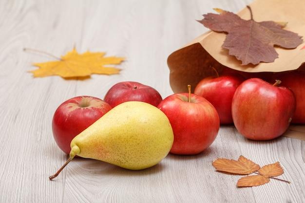 Rijpe gele peer, rode appels met papieren zak en droge bladeren op houten bureau.