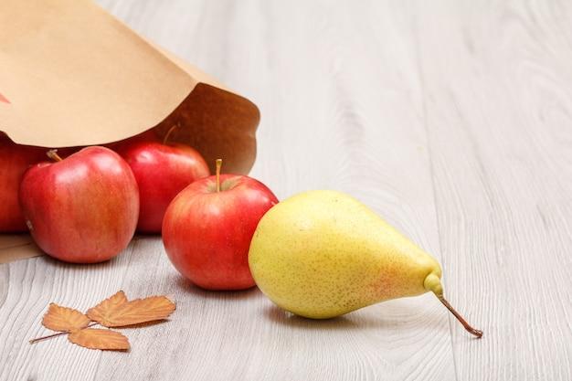 Rijpe gele peer, rode appels met papieren zak en droog blad op houten bureau. gezonde biologische voeding.