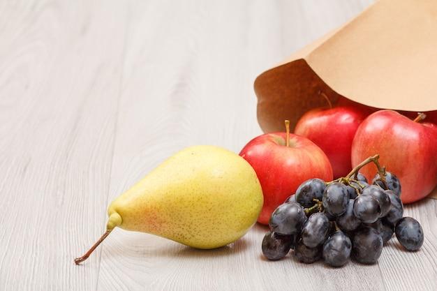 Rijpe gele peer, tros druiven en rode appels met papieren zak op houten bureau. gezonde biologische voeding.