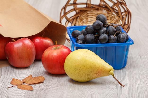 Rijpe gele peer, tros druiven in een doos, rieten mand, rode appels met papieren zak en droog blad op houten bureau. gezonde biologische voeding.