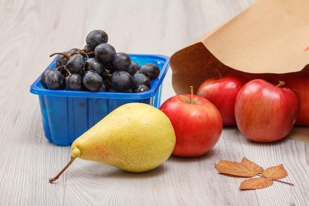 Rijpe gele peer, tros druiven in een doos, rode appels met papieren zak en droog blad op houten bureau.