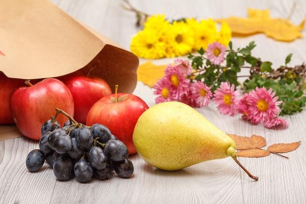 Rijpe gele peer, tros druiven, rode appels met papieren zak en bloemen op houten bureau. gezonde biologische voeding. herfst thema.