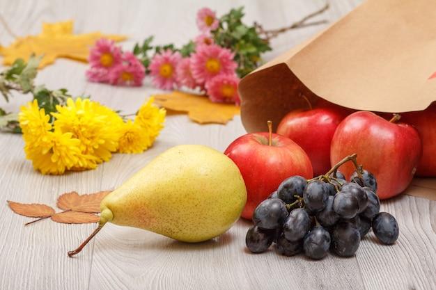 Rijpe gele peer, tros druiven, rode appels met papieren zak en bloemen op houten bureau.